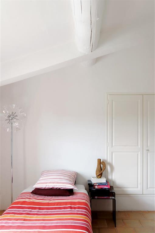 L'ambiance épurée dans cette chambre aux murs blancs et aux poutres apparentes
