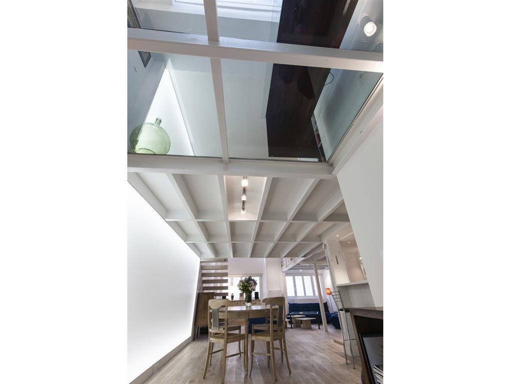 Mezzanine opaque et transparente du loft. Le plancher de verre agrandit l'espace et laisse passer la lumière zénithale.