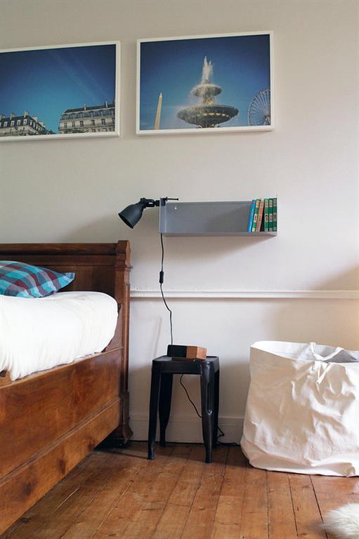 Le lit d'antiquaire en noyer posé sur le parquet d'origine apporte le chic de l'ancien dans cette chambre d'enfant rafraichie par des murs tout blancs et quelques éléments déco actuelle.