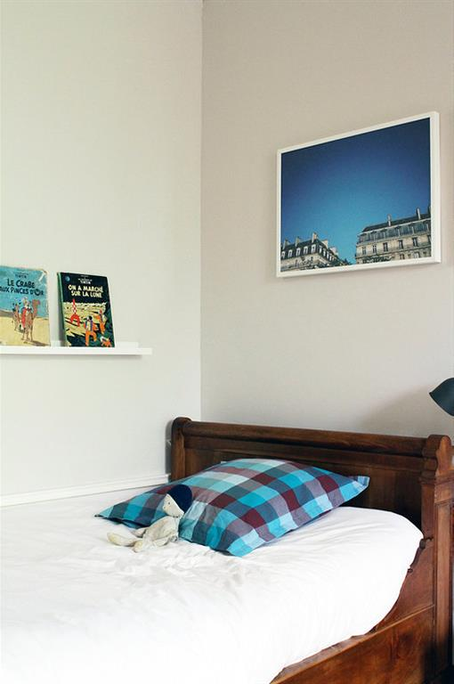 Lit d'antiquaire en noyer et murs blancs pour une chambre d'enfant sobre