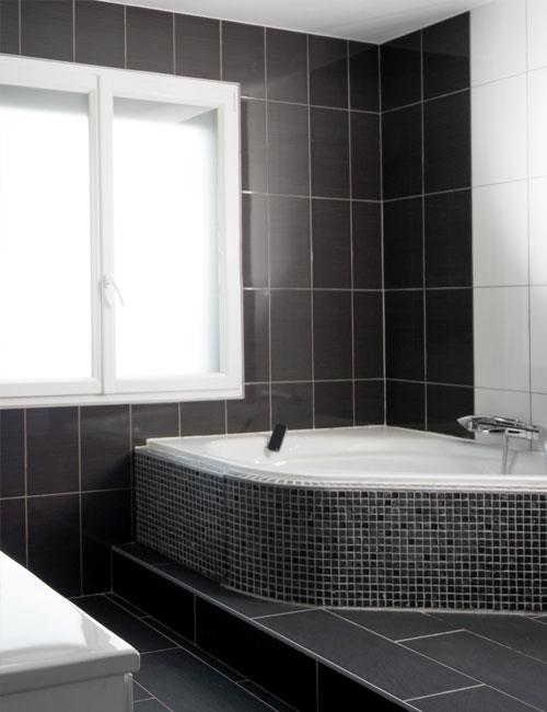 Une baignoire d 39 angle couverte de fa ence noire et grise for Faience salle de bain moderne