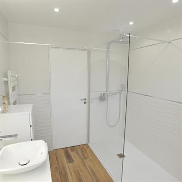 Salle de bain contemporaine blanche avec douche receveur slim, mobilier blanc, miroirs avec leds intégrés. Carrelage aspect bois au sol pour réchauffer le blanc des murs.