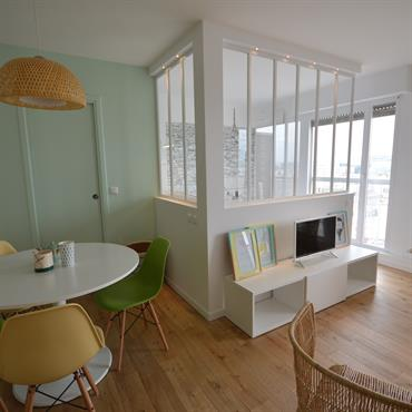 Pièce à vivre avec coin salle à manger et espace TV. Verrière de séparation avec la chambre. Parquet chêne clair naturel. Mobilier scandinave. Mur couleur vert d'eau.