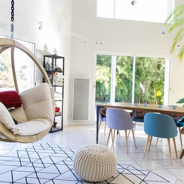 Salle à manger donnant sur le salon. Chaises et fauteuils bois et tissus colorés de style scandinave. Nacelle suspendue Amazonias Globo.