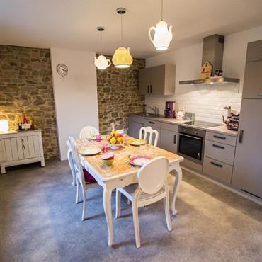 Cuisine moderne grise avec espace salle à manger mobilier classique blanc.