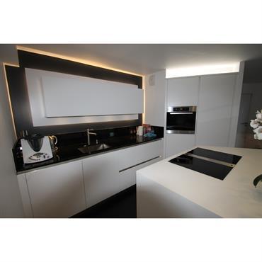 La pièce ayant une forme atypique, l'architecte d'intérieur a conçu une cuisine sur-mesure, fonctionnelle et personnalisée.  Domozoom