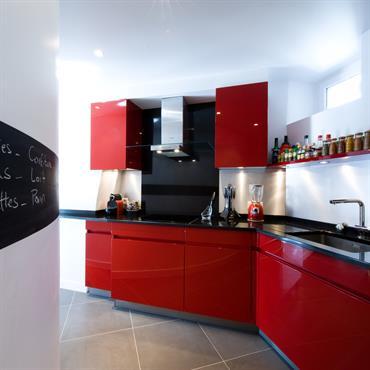 Découvrez la réalisation d'une cuisine rouge. L'architecte a du composé avec le couloir de forme arrondie.  Domozoom