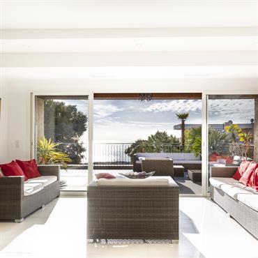 Salon orienté sur l'extérieur et impression d'être à l'extérieur grâce aux baies vitrées.
