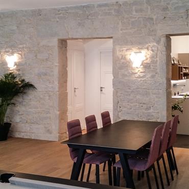 Vaste pièce à vivre avec coin salon, billard et espace salle à manger. Mur en pierres apparentes, moulures, parquet en bois clair.