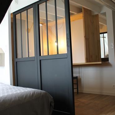 Espace chambre séparé d'une pièce à vivre par une verrière en acier coulissante