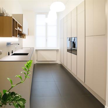 Cuisine contemporaine design en I tout en longueur. Mobilier de rangement avec façades gris mat. Grands carreaux gris foncé au sol, plan de travail slim.