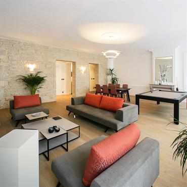 Vaste pièce à vivre avec coin salon, billard et table à manger. Mix de mobilier de design scandinave et moderne. Mur en pierres apparentes, moulures, parquet en bois clair.