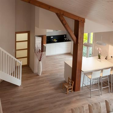 Vue de la mezzanine sur une cuisine moderne ouverte sur un espace salle à manger.
