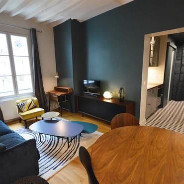 Salon au style mix & match design vintage pour une ambiance chaleureuse. Tables basses gigognes, canapé velours et mobilier vintage.