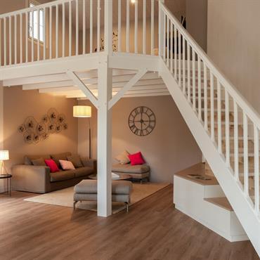 Mezzanine avec escalier et structure en bois peint blanc sur coin salon.