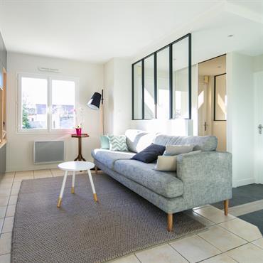 Espace salon / coin TV avec mobilier de style scandinave. Grands rangements intégrés et sur-mesure. Verrière de séparation avec l'entrée.