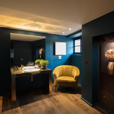 Salle de bain bois et laiton, une note d'humour pour un portrait provocateur.