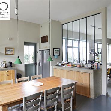 Cuisine à vivre intemporelle à l'esprit maison de famille. Sol en béton ciré, mobilier en bois. Ouverture partielle vers le salon grâce à une verrière industrielle.