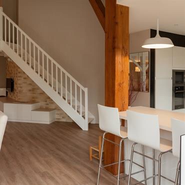 Escalier droit en bois blanc donnant sur une mezzanine.