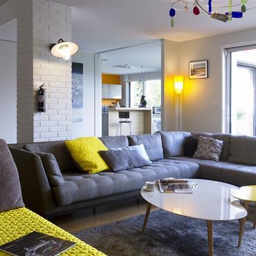 Salon ouvert vers la cuisine et le salon. Les pointes de jaune sont présentes.