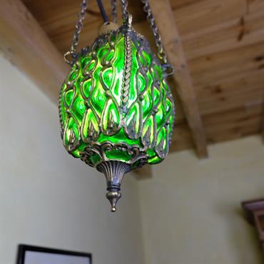 La lampe Anzû est une suspension décorative qui diffuse une jolie lumière verte. Elle est en verre soufflé et laiton, et est 100% artisanale.