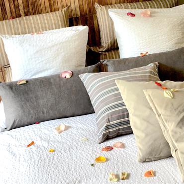Parure de lit blanche, coussins variés beiges, blancs et gris, unis et à rayures.