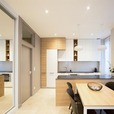Cuisine contemporaine ouverte sur salle à manger. Mobilier laqué blanc et bois, ilot central, plan de travail slim quartz noir. Placard sur mesure façade miroir.