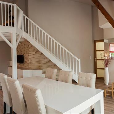 Espace de vie avec cuisine ouverte, sur salle à manger. Coin salon cosy sous une mezzanine.