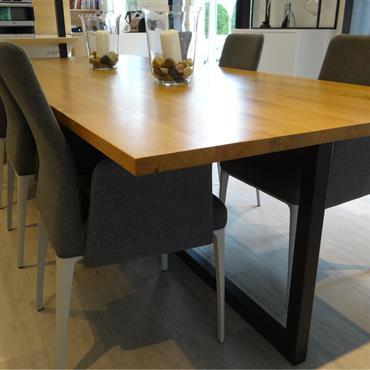 Espace salle à manger avec une grande table à manger, plateau en bois et pieds accier. Fauteuils design vintage en tissu gris.