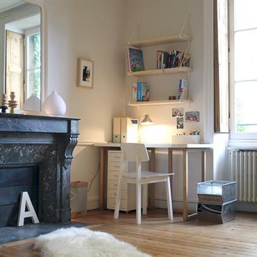 Déco naturelle et sobre pour une chambre d'enfant aménagée dans une pièce haute de plafond avec parquet et cheminée de marbre.