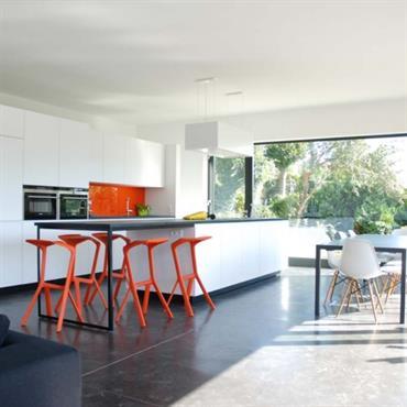 Grande cuisine ouverte sur la pièce à vivre. L'utilisation de la couleur orange relève les blanc et gris foncé.