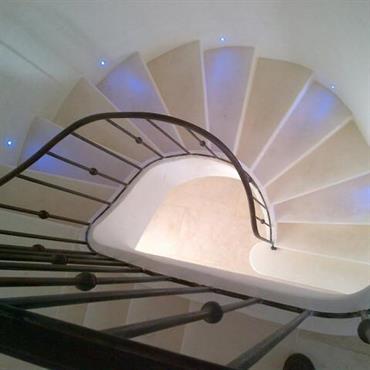 L'escalier maçonné offre un beau garde corps en fer et un éclairage bleuté au niveau des marches pour un rendu entre tendance et provençal.