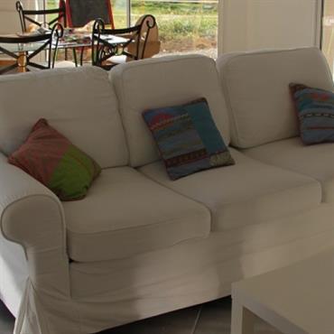 Salon avec canapé blanc et salle à manger, avec plateau en verre et chaises en fer forgé