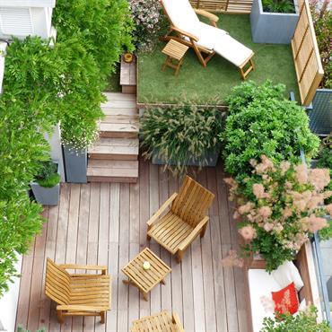 Petit jardin sur deux niveaux aménagé avec terrasses. La partie engazonnée surplombe la terrasse en bois.