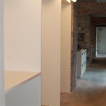 Couloir en briques rouges aménagé de rangements blancs