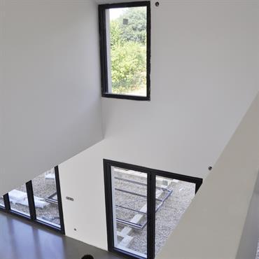 Un intérieur généreux. Depuis la passerelle menant à la chambre des parents une belle vue du jardin, et une belle double hauteur au dessus de l'espace à vivre