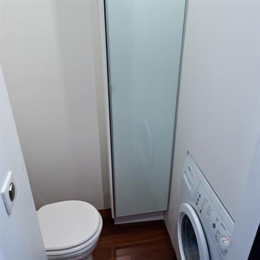 Ces toilettes intègre une machine à laver et des rangements pour rendre l'espace fonctionnel.