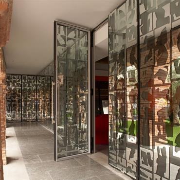 Le mur de verre est imprimé d'une sérigraphie à base de résidus argentés qui mirent et diffractent le gras de la terre cuite.