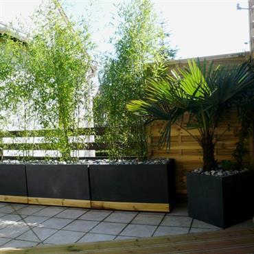 Terrasse de ville paysagée avec jardinières en métal et bambous brise vue.