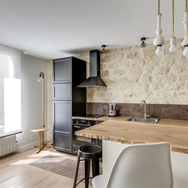 Moderne et rustique grâce au mur de pierre et au plan de travail en bois travaillé