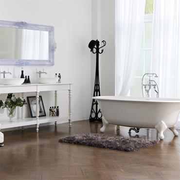 Baignoire îlot aux lignes classiques arrondies présentée dans une salle de bain avec parquet