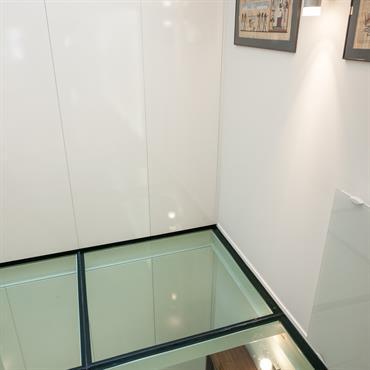 Le plancher de verre augmente les perspectives et souligne l'alignement des portes des rangements du rez-de-chaussée et de la mezzanine.
