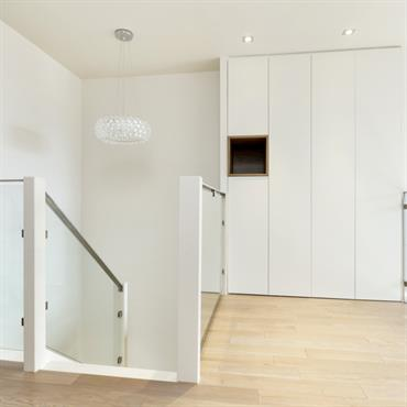 Arrivée d'escalier lumineuse, placard aux portes coplanaires et niche réhaussée par le bois teinté huilé