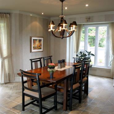 Salle à manger avec table en bois rectangulaire. Chaise de style ethniques. La couleur de l'ensemble est de bois assez sombre, la pièce à des murs clairs, blancs et crèmes ...