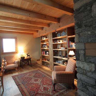Grande pièce bureau avec fauteuil et bibliothèque. Tapis de style ancien, poutres apparentes et mobilier en bois