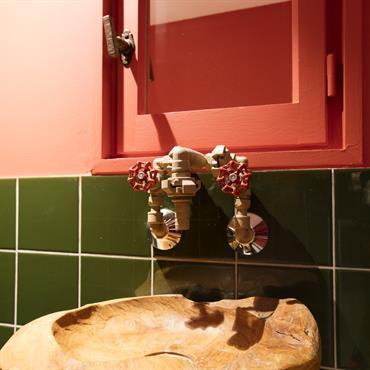 Coin lavabo très original avec robinet industriel et vasque en bois sculpté