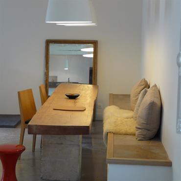 L'aspect authentique et moderne de cette pièce est donné par la table en bois et pierre brute, ainsi que le sol en pierre