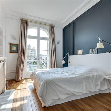 Tête de lit laquée blanc équippée de deux liseuses Artémide qui éclairent le lit de part en part.