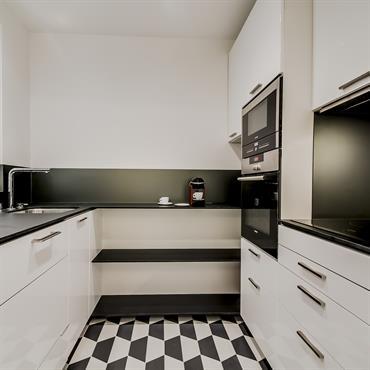 Cuisine en U avec meubles blancs et plans de travail en stratifié noir