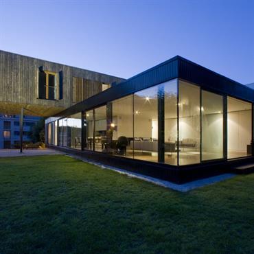 Le volume inférieur contient les pièce à vivres communes. Les baies vitrées les ouvrent sur le jardin.
